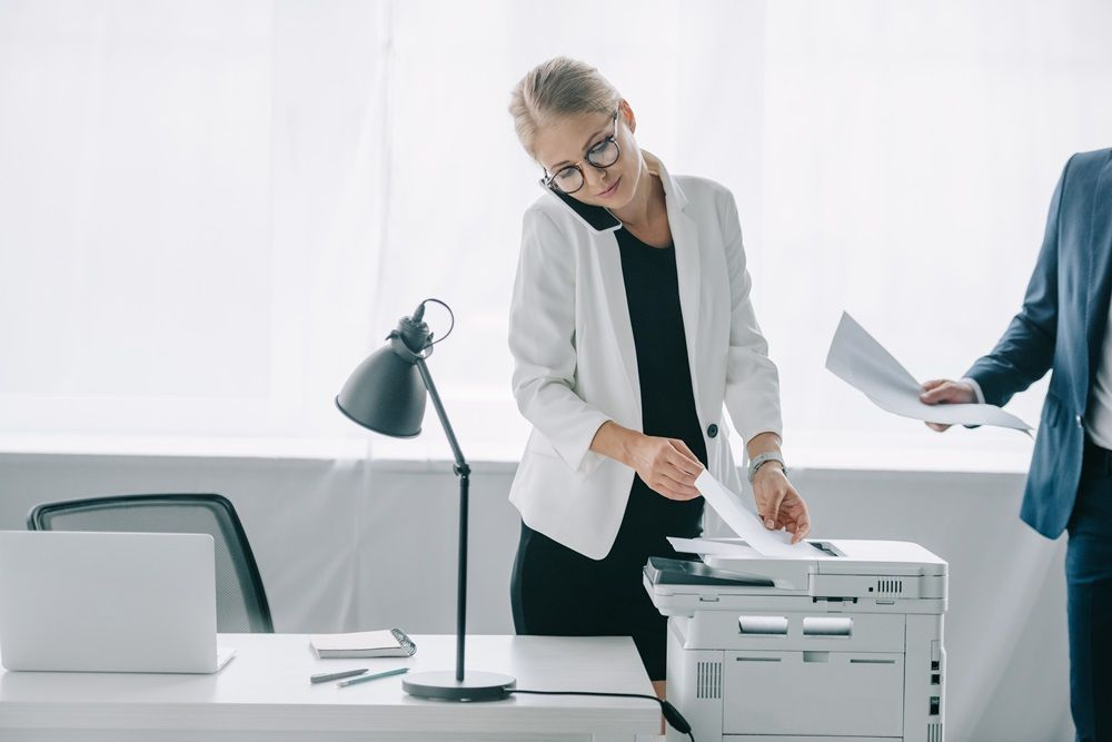 Woman picking up a sheet of paper from a printer